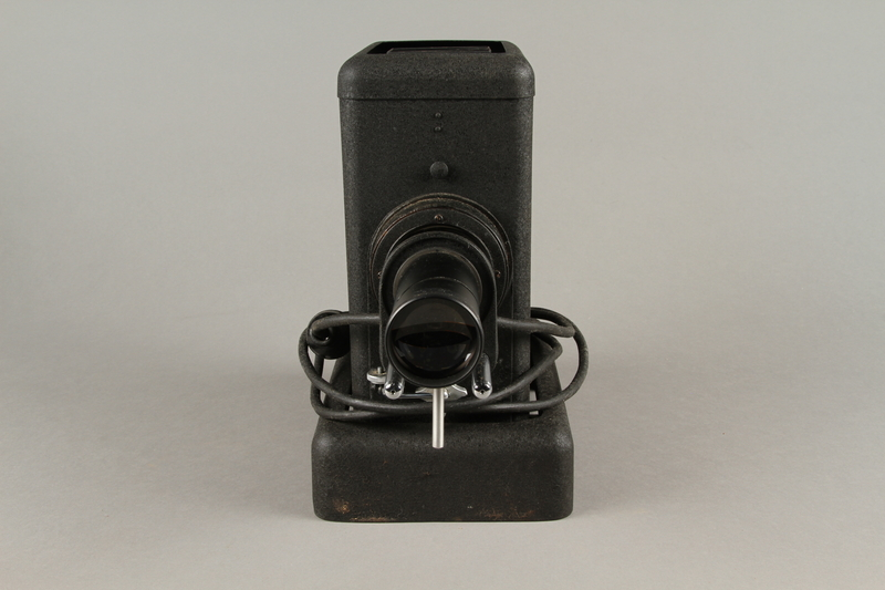 2009.372.5 a front Leitz glass slide projector with case, trays, and key ring used in a displaced persons camp