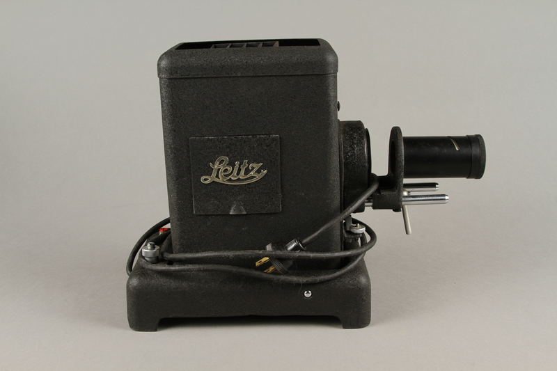 2009.372.5 a right Leitz glass slide projector with case, trays, and key ring used in a displaced persons camp