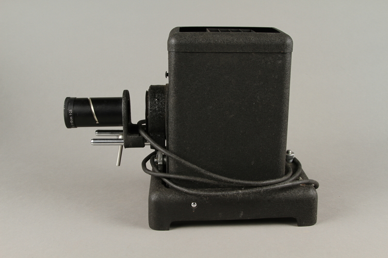 2009.372.5 a left Leitz glass slide projector with case, trays, and key ring used in a displaced persons camp