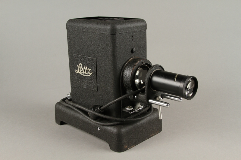 2009.372.5 a 3/4 view Leitz glass slide projector with case, trays, and key ring used in a displaced persons camp