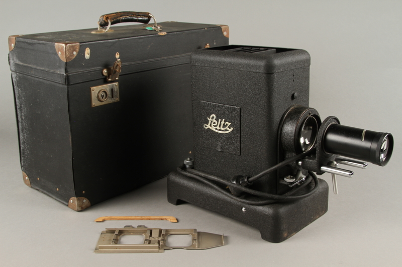 2009.372.5 a-e front Leitz glass slide projector with case, trays, and key ring used in a displaced persons camp