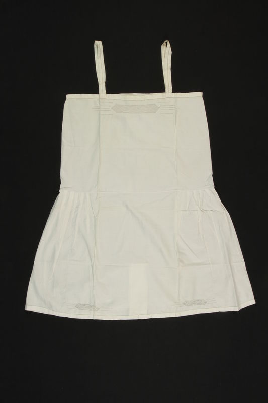 2009.376.8 front White embroidered cotton slip with an NS monogram and interior flap brought to the US by a Jewish family fleeing German occupied Poland