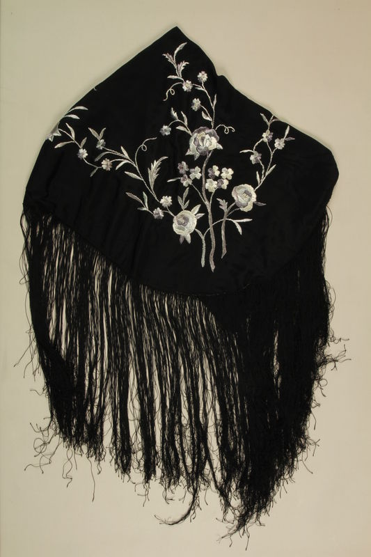 2009.376.5 front Fringed black silk piano shawl with embroidered silver flowers brought to the US by a Jewish family fleeing German occupied Poland