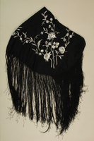 2009.376.5 front Fringed black silk piano shawl with embroidered silver flowers brought to the US by a Jewish family fleeing German occupied Poland  Click to enlarge