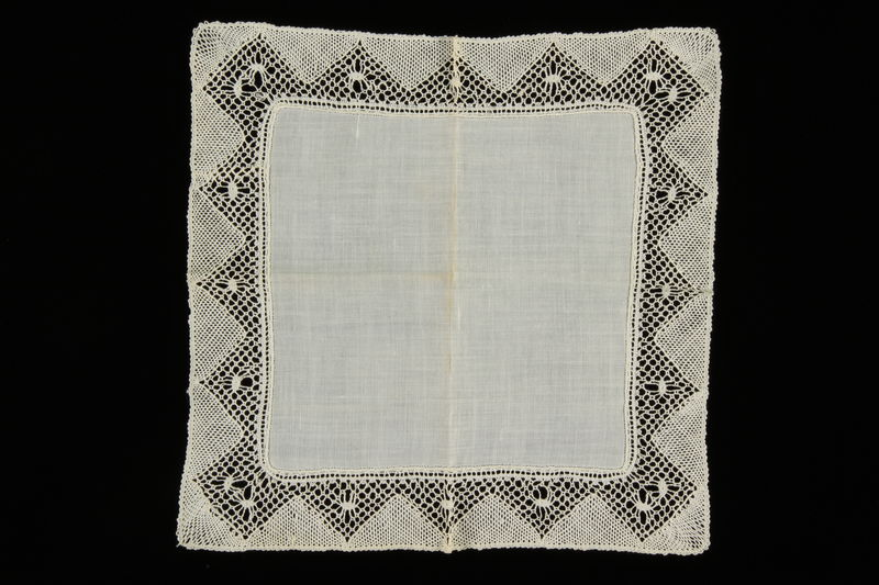 2009.376.33 front White handkerchief with an embroidered triangle patterned border brought to the US by a Jewish family fleeing German occupied Poland
