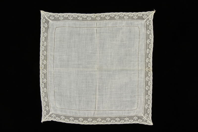 2009.376.34 front White cotton lace handkerchief with a floral motif lace border brought to the US by a Jewish family fleeing German occupied Poland