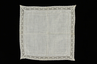 2009.376.34 front White cotton lace handkerchief with a floral motif lace border brought to the US by a Jewish family fleeing German occupied Poland  Click to enlarge