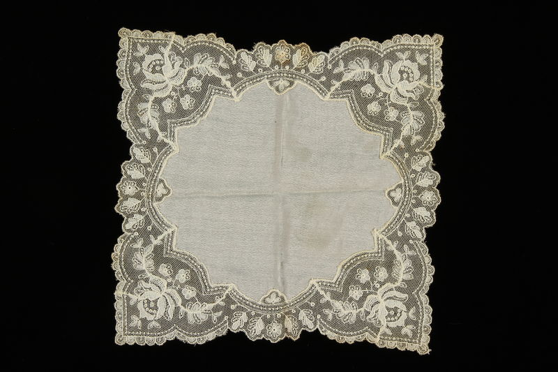 2009.376.36 front White silk handkerchief with handmade floral lace design brought to the US by a Jewish family fleeing German occupied Poland