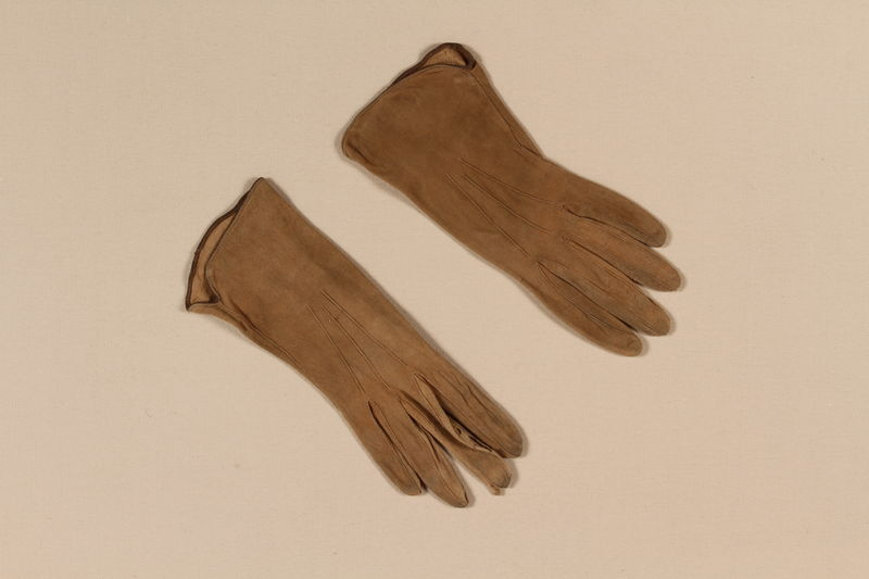 2009.376.29_a-b front Pair of woman's fawn and tan suede gloves brought to the US by a Jewish family fleeing German occupied Poland