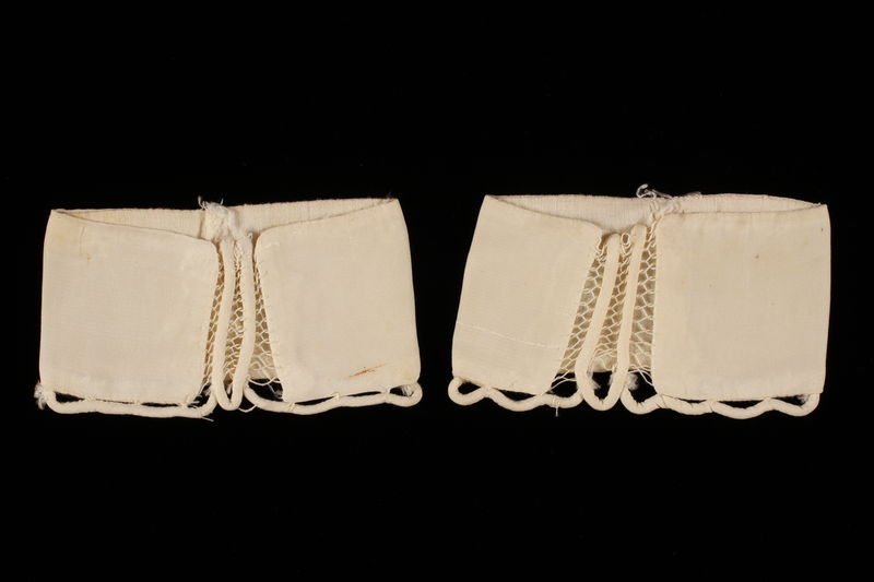 2009.376.18_a-b front Two white silk sleeve cuffs with scalloped cording brought to the US by a Jewish family fleeing German occupied Poland