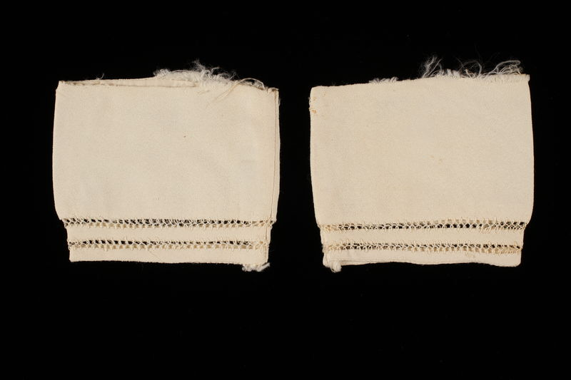 2009.376.19_a-b front Two white silk sleeve cuffs with stitched whitework borders brought to the US by a Jewish family fleeing German occupied Poland