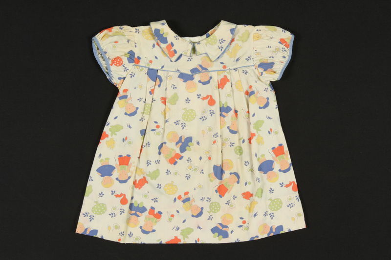 2009.376.23 front Child's colorful print cotton dress with blue piping brought to the US by a Jewish family fleeing German occupied Poland