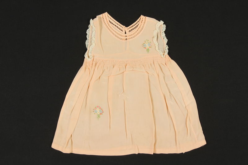2009.376.25 front Child's peach silk sleeveless dress with embroidered flowers brought to the US by a Jewish family fleeing German occupied Poland
