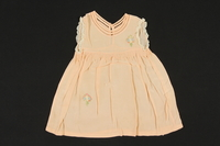 2009.376.25 front Child's peach silk sleeveless dress with embroidered flowers brought to the US by a Jewish family fleeing German occupied Poland  Click to enlarge