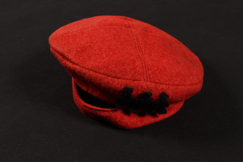 2010.194.6 front Red wool felt cap with stick figure silhouettes worn by a young Austrian Jewish refugee to the US
