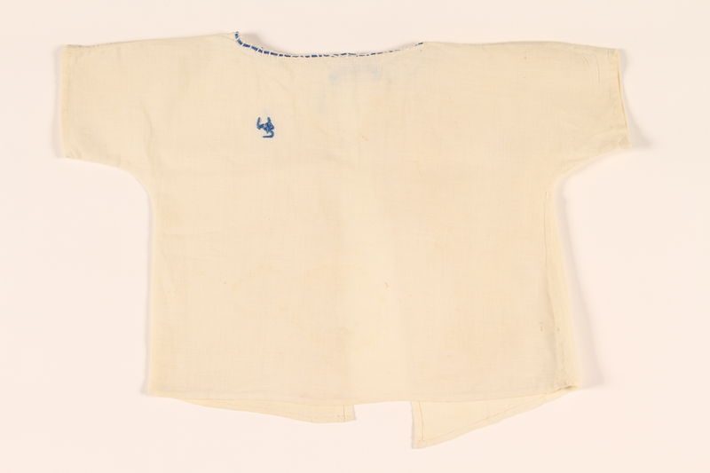 2010.337.2 front Infant's open back blouse with blue monogram made in DP camp