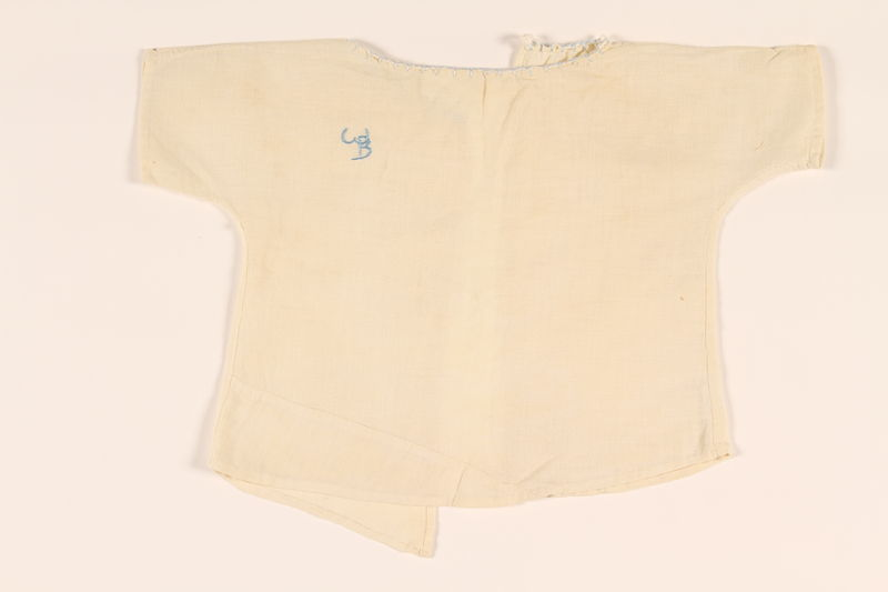 2010.337.3 front Infant's open back white blouse with a light blue monogram made in DP camp