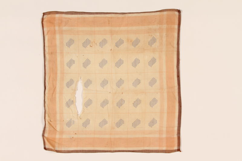 2008.228.3 front Beige and orange embroidered linen napkin used in the Warsaw ghetto