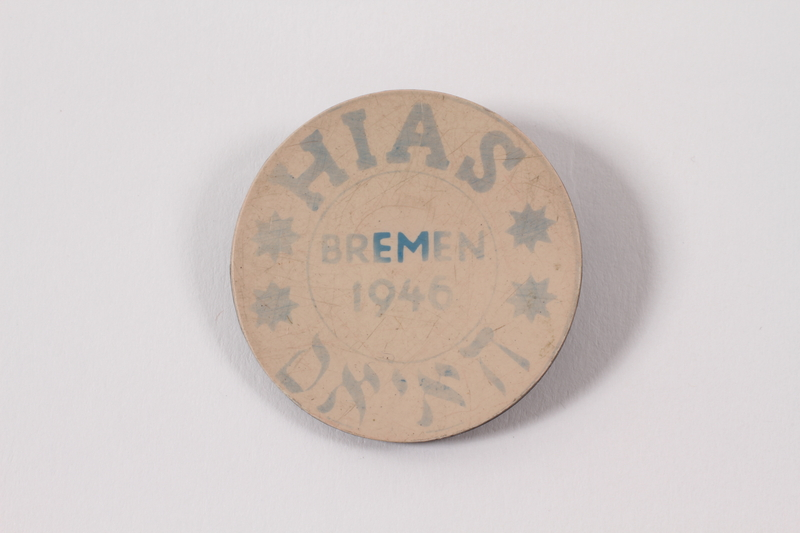 2010.416.1 a front Souvenir pin with the words HIAS and Bremen and two boxes given to a young Jewish Polish refugee