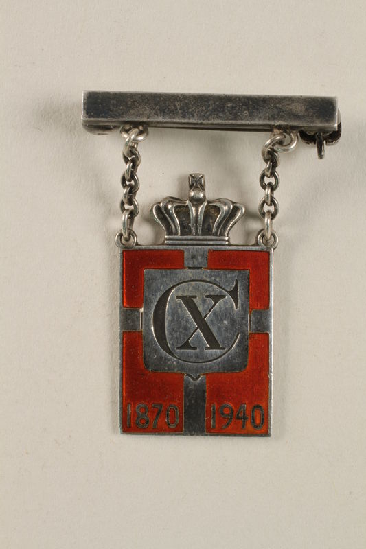2010.417.1 front Kingmark silver and red enamel pin with chains on a pinbar commemorating the 70th birthday in 1940 of King Christian X of Denmark