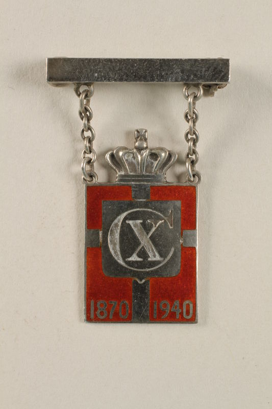 2010.417.2 front Kingmark silver and red enamel pin with chains on a pinbar commemorating the 70th birthday in 1940 of King Christian X of Denmark