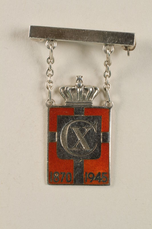 2010.417.3 front Kingmark silver and red enamel pin with chains on a pinbar commemorating the 75th birthday in 1945 of King Christian X of Denmark