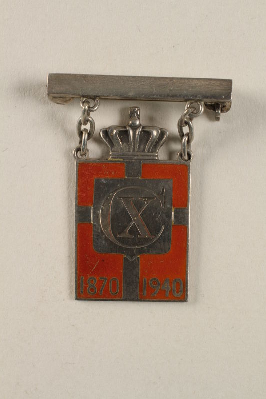 2010.417.7 front Kingmark silver and red enamel pin with chains on a pinbar commemorating the 70th birthday in 1940 of King Christian X of Denmark