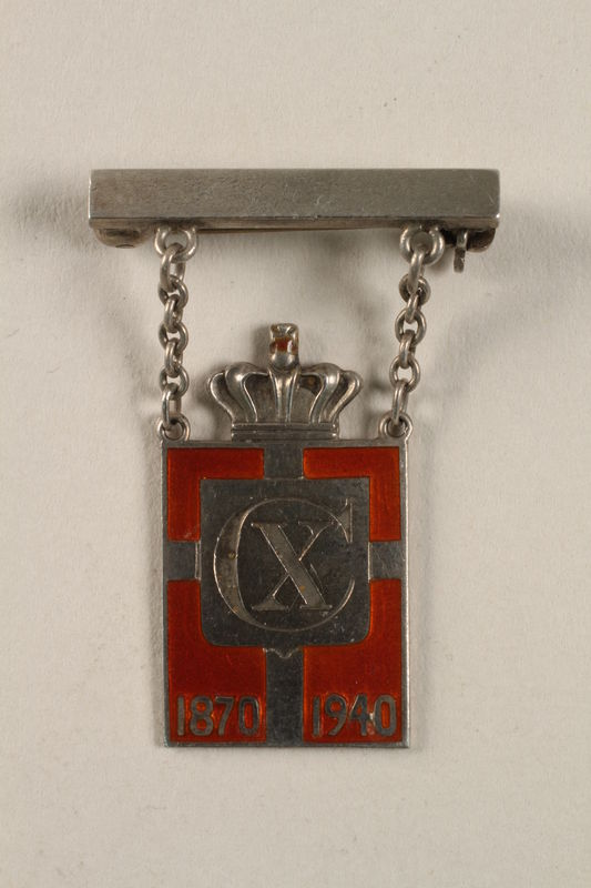 2010.417.8 front Kingmark silver and red enamel pin with chains on a pinbar commemorating the 70th birthday in 1940 of King Christian X of Denmark