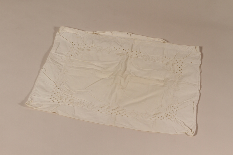 2010.442.12 front White pillowcase embroidered with a floral design recovered by a Hungarian Jewish woman from her neighbors