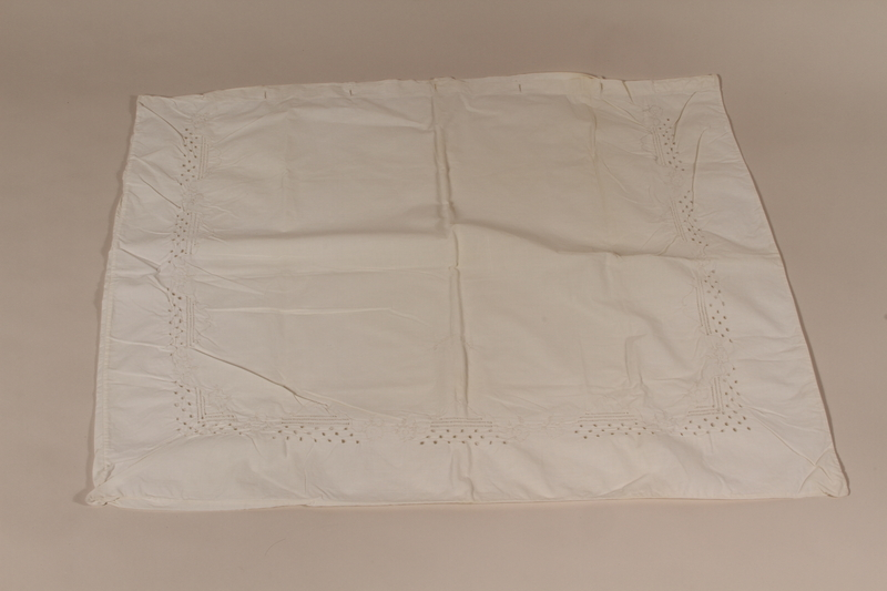 2010.442.13 front Large white pillowcase embroidered with a floral design recovered by a Hungarian Jewish woman from her neighbors