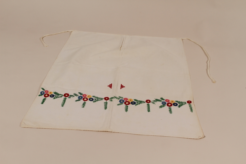 2010.442.14 front Apron with a garland of multicolored floral embroidery recovered by a Hungarian Jewish woman from her neighbors