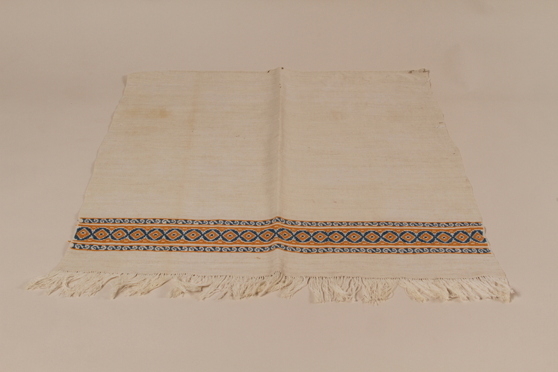 2010.442.16 front Fringed apron with a band of blue and yellow geometric embroidery recovered by a Hungarian Jewish woman from her neighbors