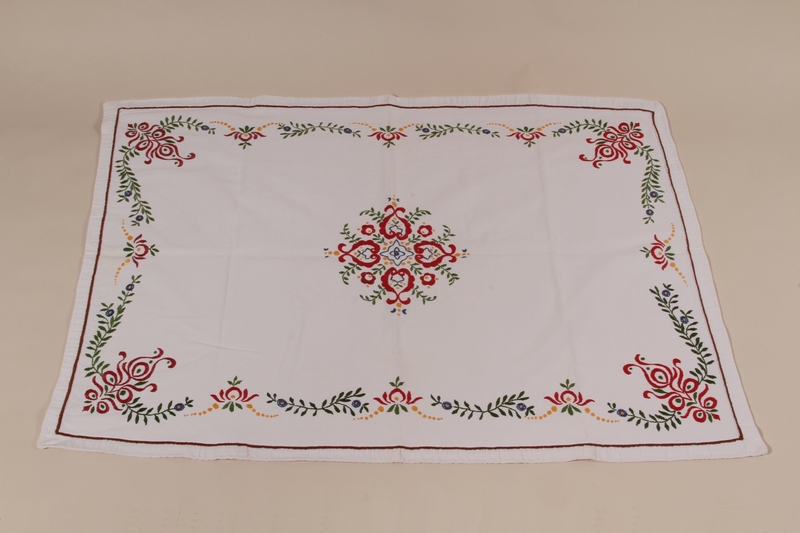 2010.442.18 front Tablecloth with an embroidered multicolored floral design recovered by a Hungarian Jewish woman from her neighbors