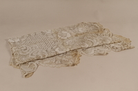 2010.442.19 front Lace tablecloth with an embroidered white floral design recovered by a Hungarian Jewish woman from her neighbors  Click to enlarge