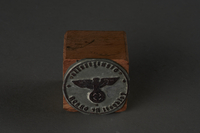 2010.441.2 front Circular metal stamp with Nazi seal and Reichsadler on a block mount used by a Dutch resistance member to forge identity cards  Click to enlarge