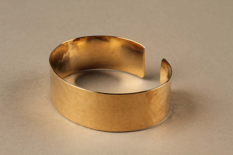 2010.484.2 a side b Adjustable cuff bracelet made from gold marks with pouch owned by German Jewish refugee