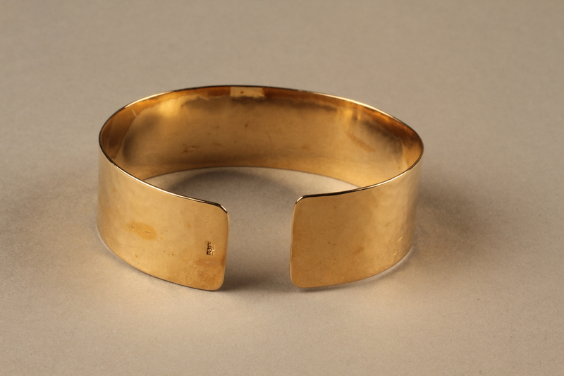 2010.484.2 a side c Adjustable cuff bracelet made from gold marks with pouch owned by German Jewish refugee