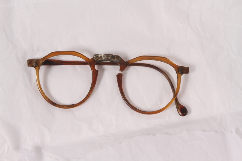 2010.494.2 a front Plastic eyeglass frames, temple and lenses worn by a Jewish concentration camp inmate