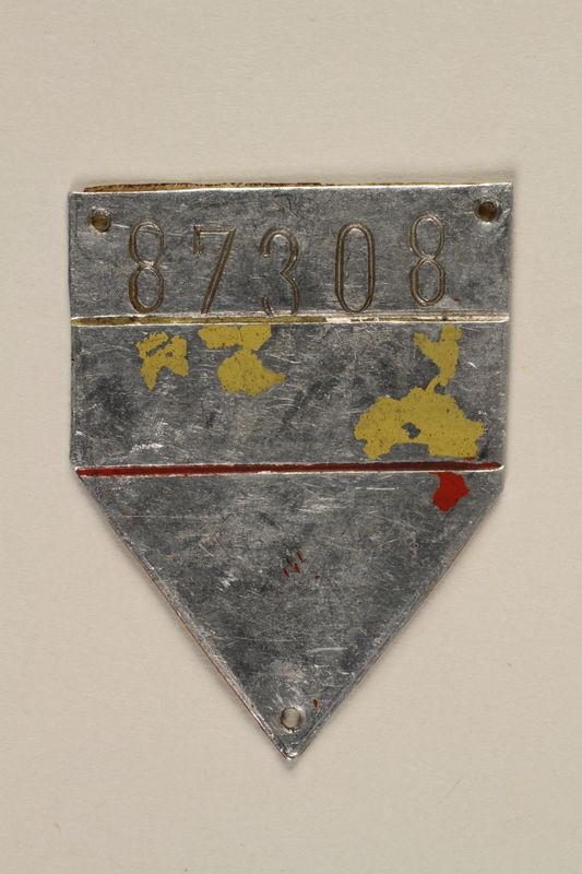 2010.494.3 front Metal ID badge with number 87308 issued to a Jewish prisoner