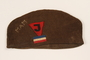 Brown knit hat with a J triangle patch and initials worn by a Yugoslavian political prisoner