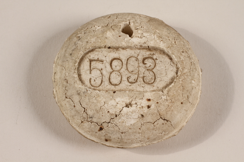 2003.112.19 front Crematorium tag, number 5893, acquired at Dachau postwar by a US soldier