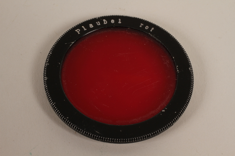 2003.149.42_d front Four Plaubel color camera filters, lens, and case used by German Jewish US soldier