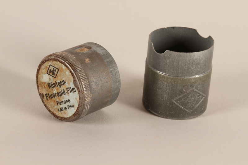 2003.149.49_a-b open Agfa metal film canister used by German Jewish US soldier