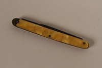 2003.149.68 front Pocket knife with yellow plastic handle used by German Jewish US soldier  Click to enlarge