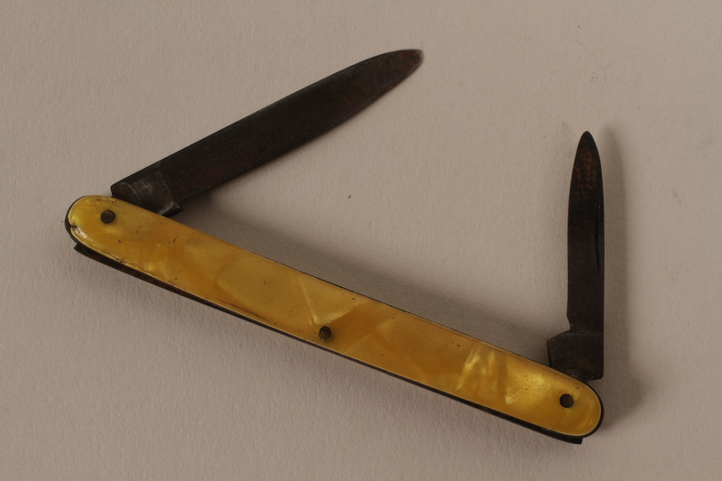 2003.149.68 open Pocket knife with yellow plastic handle used by German Jewish US soldier