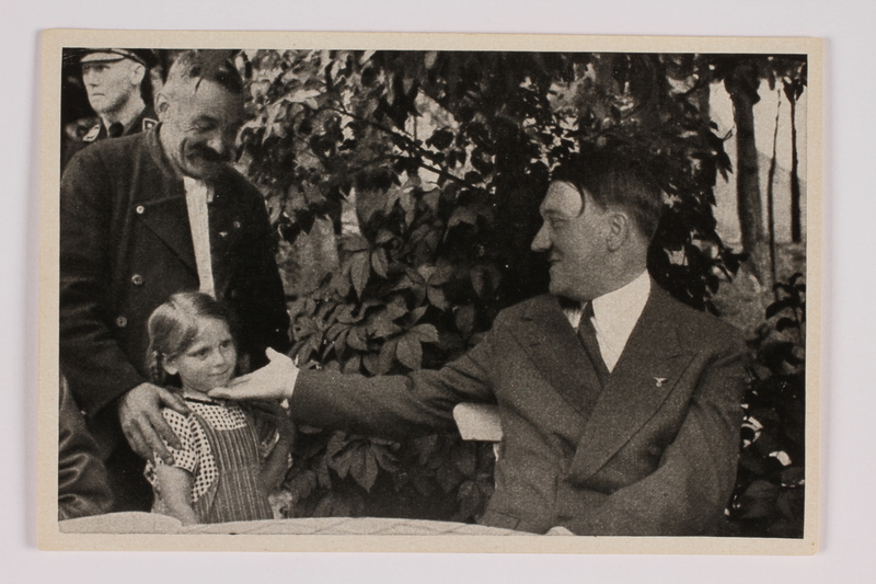 2012.68.4 front Cigarette card photo of Hitler greeting a young girl and her grandfather