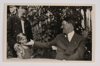 2012.68.4 front Cigarette card photo of Hitler greeting a young girl and her grandfather  Click to enlarge