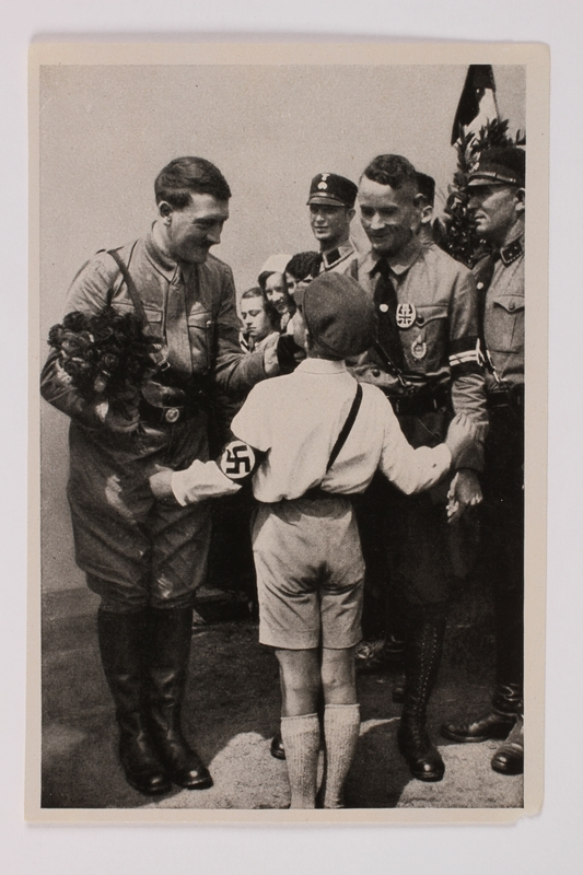 2012.68.9 front Cigarette card photo of a smiling Hitler with roses and a Hitler Youth member