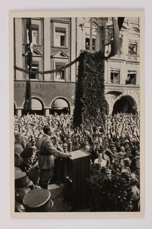 2012.68.10 front Cigarette card photo of Hitler addressing a large crowd