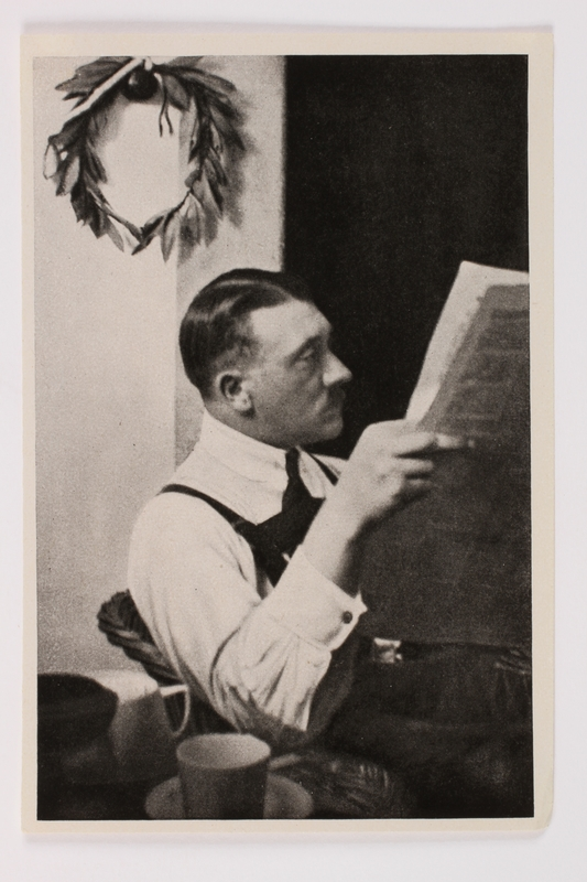 2012.68.11 front Cigarette card photo of Hitler reading the newspaper